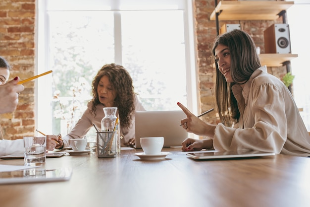 議論。チームと現代のオフィスで若いビジネス女性。創造的な会議、タスクを与える。フロントオフィスで働く女性。金融、ビジネス、女の子の力、インクルージョン、多様性、フェミニズムの概念。