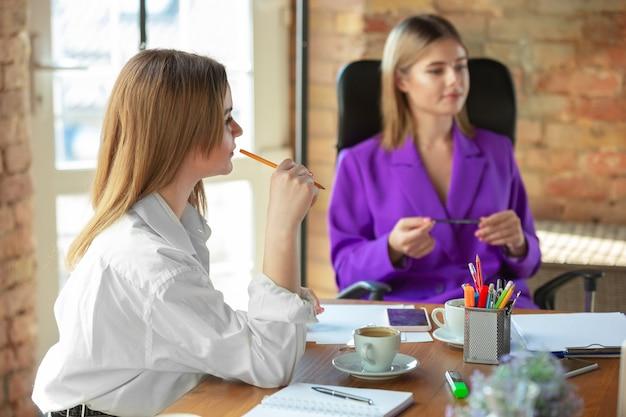 Discussione. giovane donna caucasica di affari in ufficio moderno con la squadra. incontro, assegnazione di compiti. donne al lavoro di front-office. concetto di finanza, affari, potere della ragazza, inclusione, diversità, femminismo.