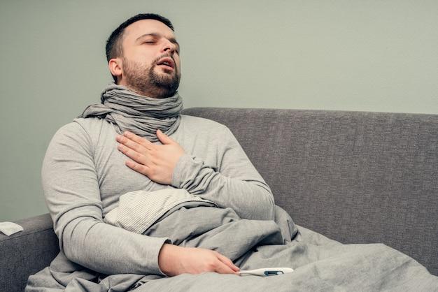 Болезнь. болеем дома. молодой человек болен, лечится дома. боль в груди, затрудненное дыхание. дует нос в салфетку, насморк. инфекция, эпидемия, бактерионоситель.