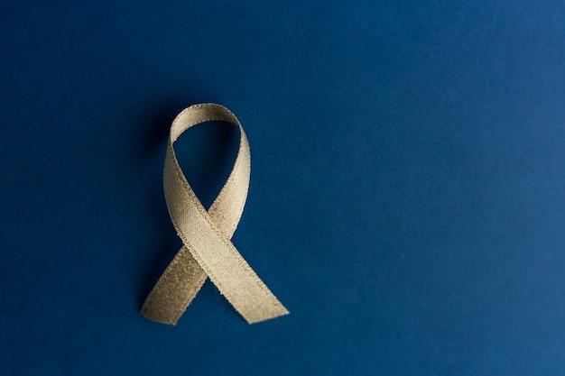 Disease control concept. golden ribbon on dark blue background, top view, copy space