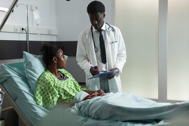 병동에서 젊은 아프로 환자와 함께 앉아 질병 의사