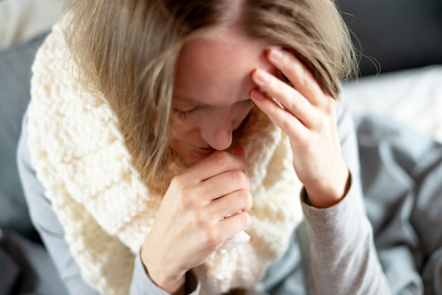 Disease. home treatment. flu and the common cold. a woman is sick at home, runny nose and flu.