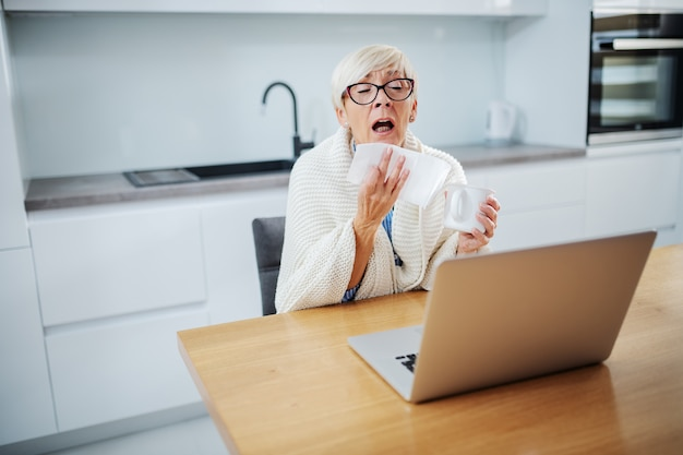 Diseased attractive senior woman sitting in kitchen covered with blanket, holding mug with tea and sneezing
