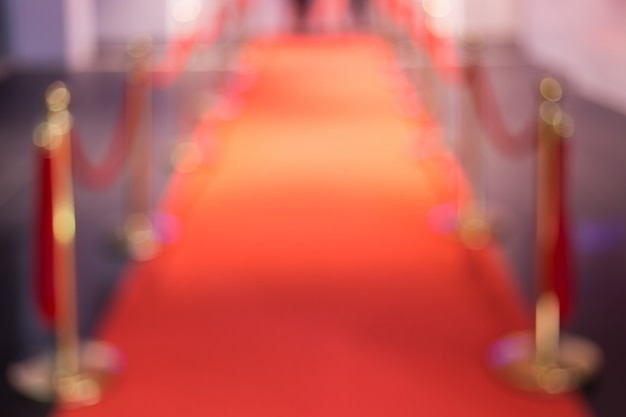 Disfocus of the red carpet between rope barriers in the success party