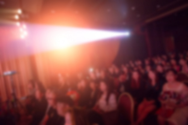 Disfocus of speakers on the stage under the color full of downlight