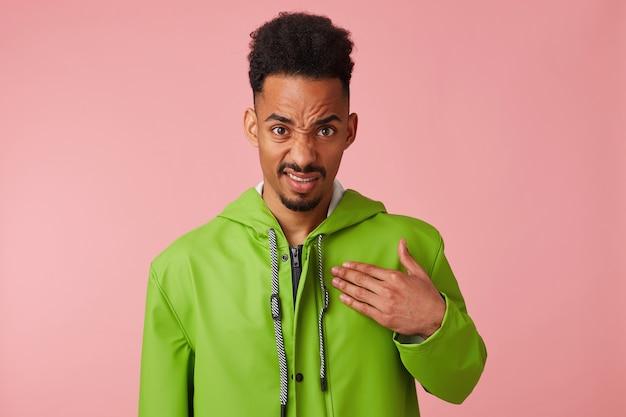 Раздраженный и возмущенный заявлениями босса, красивый темнокожий парень недовольно хмурится, носит зеленый дождевик, показывает на себя руку, встает.