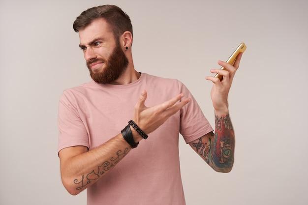 불만을 품은 수염 난 문신을 한 남자가 짧은 머리를 가진 짧은 머리로 스마트 폰을 귀에서 멀리하고, 전화로 불쾌한 이야기를하고, 얼굴을 찌푸리고 흰색 입술을 접습니다.