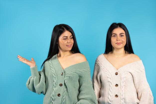 青い背景に対してポーズをとって不機嫌な白人の双子の女の子