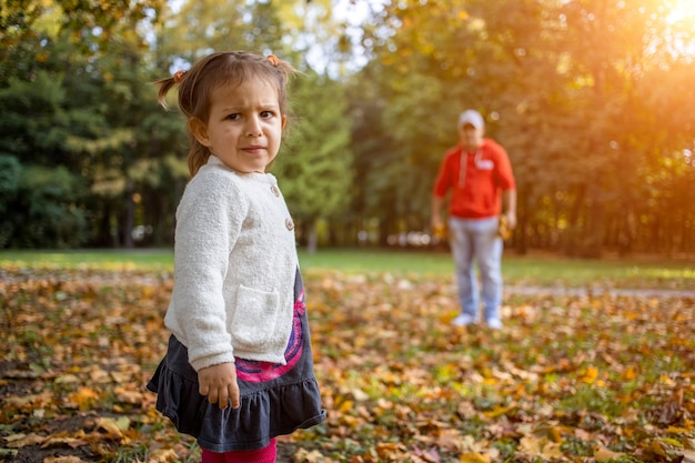 Disgruntled child in the park with dad angry girl in the park looks at the camera father and
