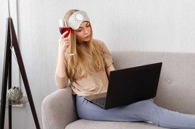 와인 한잔과 함께 불만을 품은 감정적 인 소녀가 그녀의 노트북으로 보입니다.