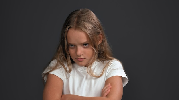 Disgruntled girl crossed her arms looking to side. teen model expresses sad emotion. problem concept