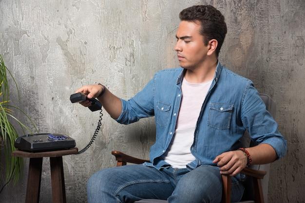 受話器を持って椅子に座っている不機嫌そうな男。高品質の写真
