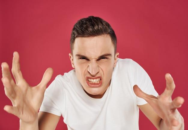 手で身振りで示す白いtシャツに怒った表情で不満を抱いた男。高品質の写真