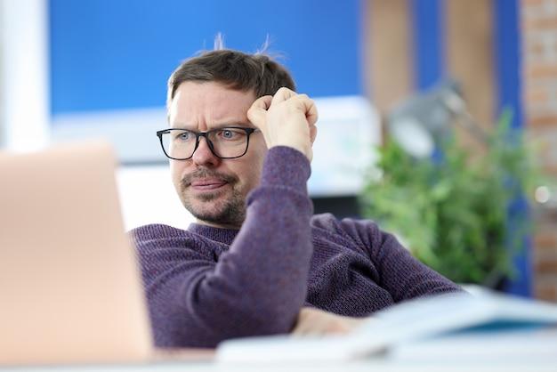 ノートパソコンの画面を見ている眼鏡をかけて不満を持った男。仕事のコンセプトでの問題