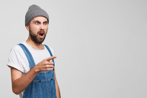Disgruntled outraged angry man stands sideways