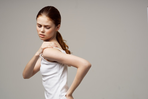 Disgruntled woman arm pain arthritis chronic disease light background