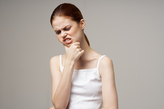 Disgruntled woman dentistry dental pain closeup light background