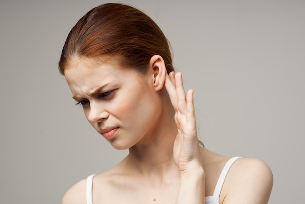Disgruntled woman holding her ear health problems