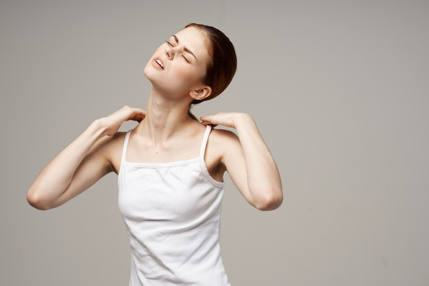 Disgruntled woman holding on to the neck health problems joint light background. high quality photo