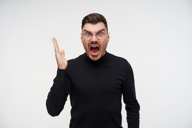Giovane uomo barbuto del brunette scontento con taglio di capelli corto che alza eccitato la sua mano mentre urla con rabbia con la bocca larga aperta, isolato su bianco
