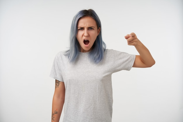 Disgruntled young blue haired tattooed female in grey basic t-shirt showing angrily with raised index finger while standing on white