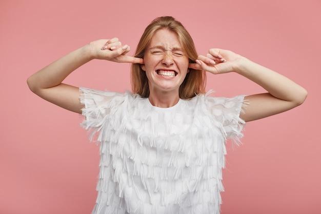 Femmina giovane rossa scontenta con trucco naturale che tiene gli occhi chiusi mentre aggrotta le sopracciglia, chiude le orecchie con le dita indice evitando suoni forti, isolato su sfondo rosa