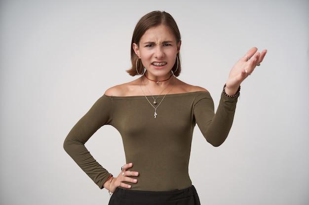 不満を持って若い短い髪のブルネットの女性は、白い壁に隔離され、正面を不満に見ながら手を上げたままカジュアルな髪型をしています
