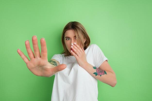실망. 녹색 스튜디오 벽에 격리된 백인 젊은 여성의 초상화