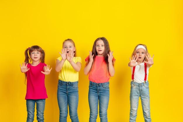 Disguasted. 행복한 아이들이 놀고 노란색 스튜디오 배경에 함께 재미. 밝은 옷을 입은 백인 아이들은 장난스럽고, 웃고, 웃고 있습니다. 교육, 어린 시절, 감정의 개념.