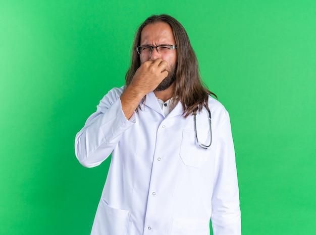 Disgustato medico maschio adulto che indossa una tunica medica e uno stetoscopio con gli occhiali che guarda la telecamera facendo un gesto di cattivo odore isolato sul muro verde