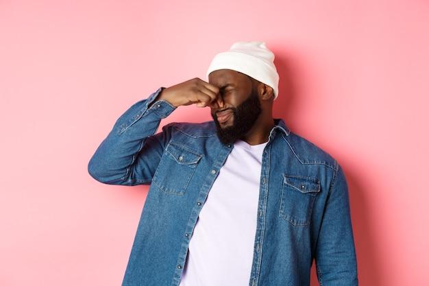 うんざりしたアフリカ系アメリカ人の男は嫌悪感から鼻を閉じ、ひどい悪臭に不満を抱き、ピンクの背景の上にビーニーとデニムのシャツを着て立っていた