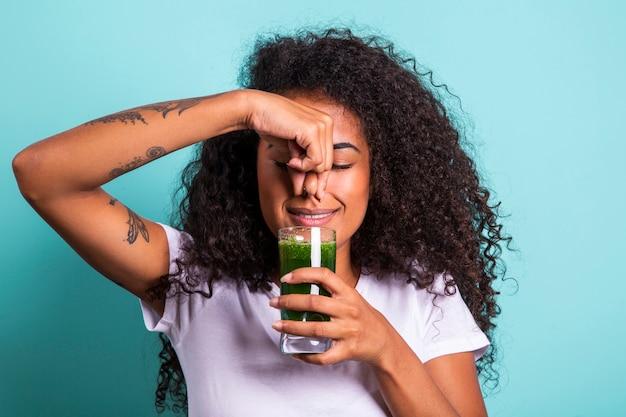 나쁜 맛으로 야채 주스를 시음하는 역겨운 아프리카 여성