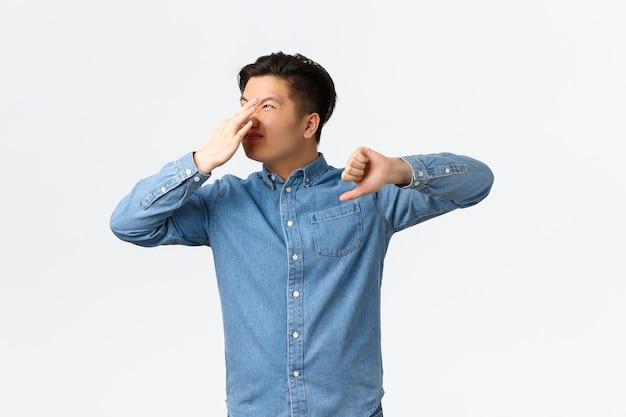 Uomo asiatico disgustato che distoglie lo sguardo e si chiude il naso con le dita, mostrando il pollice verso il basso, lamentandosi di un terribile puzzo, qualcosa che puzza, infastidito dal cattivo odore, in piedi su sfondo bianco