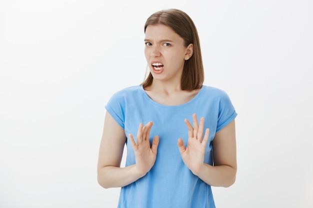 うんざりした気になる女性が顔をゆがめ、嫌悪感から身をかがめ、拒絶を示し、ジェスチャーをやめる