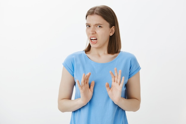 Disgusted bothered woman grimacing, cringe from aversion and show refusal, stop gesture