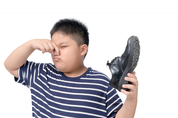 Отвращение мальчик держит пару вонючих кожаных ботинок