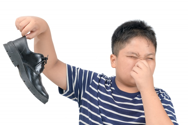 Disgusted boy holding a pair of smelly leather shoes