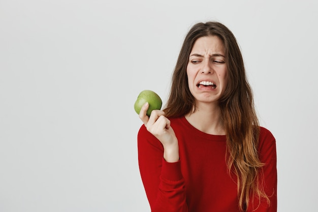 Disgusted cute woman looking at apple with aversion and dislike, grimacing