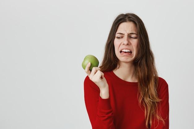 Чувствующая отвращение милая женщина смотрит на яблоко с отвращением и неприязнью, морщась