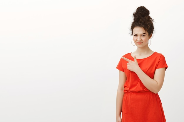 Disgusted european female in stylish casual red dress