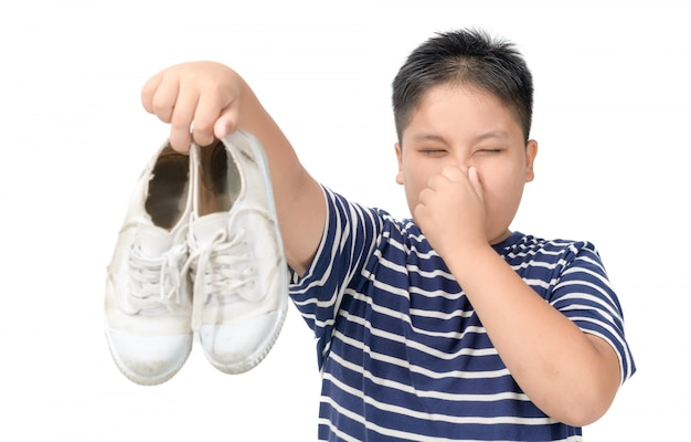 Disgusted fat boy holding a pair of smelly shoes