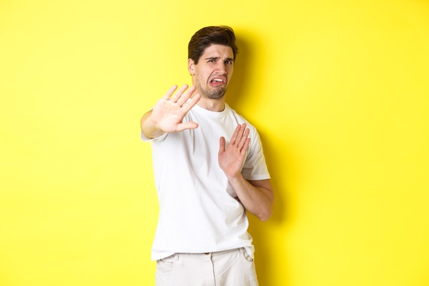 Disgusted man refusing, grimacing from dislike and aversion, begging to stop, standing in white t-shirt against yellow background.