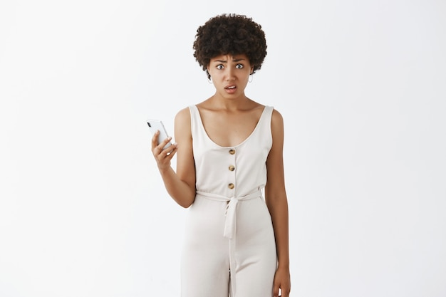 Ragazza alla moda disgustata che posa contro il muro bianco