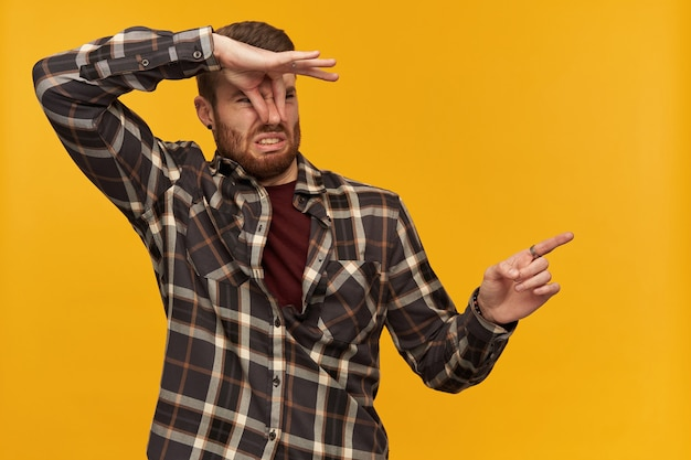 Disgusted unhappy young bearded man in plaid shirt pinches nose by hand feels bad smell or stink and pointing away to the side at empty space over yellow wall