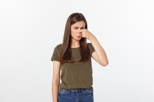 Disgusted young blonde closing her nose with her fingers. isolated over white background.