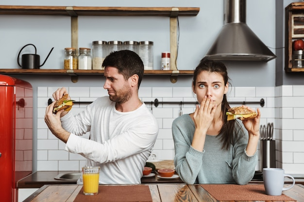Disgusted young couple sitting at the kitchen during breakfast at home, holding sandwiches