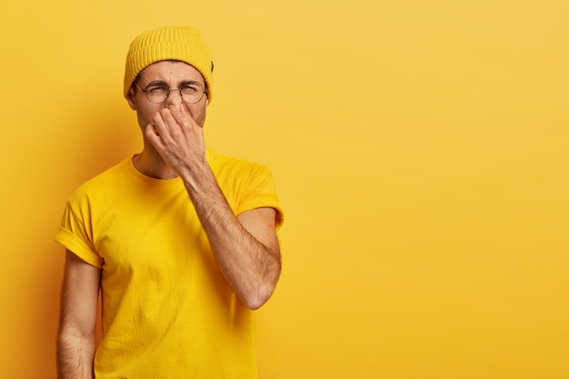 Disgusted young hipster pinches nose with fingers, looks in disgust as smells something stink, wears spectacles, yellow hat