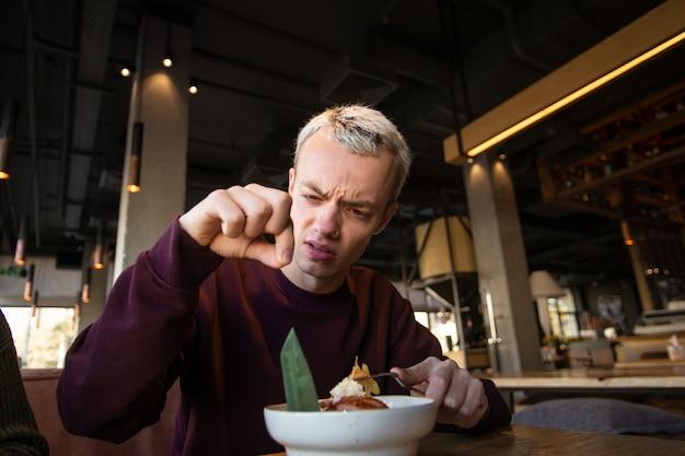 うんざりした青年がカフェで食事中に髪の毛を見つけ、嫌悪感を持って見ている