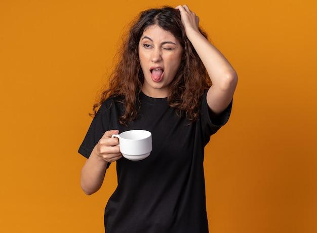 Disgustata giovane ragazza carina che tiene una tazza di tè tenendo la mano sulla testa guardando il lato che mostra la lingua con un occhio chiuso