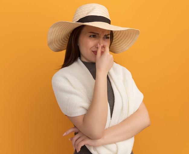 Disgustata giovane bella donna che indossa un cappello da spiaggia che fa un gesto di cattivo odore guardando il lato isolato sul muro arancione